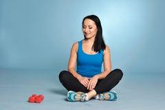 Атлетическая девушка при тело мышцы сидя на поле Стоковая Фотография