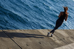 Атлетическая девушка jogging над изумительной большой предпосылкой волн на солнечном дне Стоковое Фото
