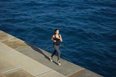 Атлетическая девушка jogging над изумительной большой предпосылкой волн на солнечном дне Стоковое Изображение