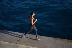Атлетическая девушка jogging над изумительной большой предпосылкой волн Стоковые Фото