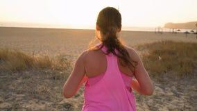 Атлетическая женщина бежать вдоль пляжа к океану акции видеоматериалы