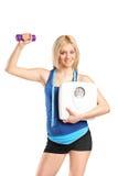 Атлетическая женщина держа масштаб гантели и веса Стоковое фото RF