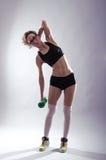 Атлетическая женщина с гантелью в руке делает наклоны Резвитесь вы Стоковая Фотография RF
