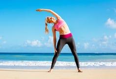 Атлетическая женщина фитнеса протягивая на пляже, стоковое фото rf
