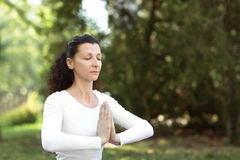 Атлетическая и взрослая женщина делая практику с namaste - концепцию йоги здорового живущего и естественного баланса на зеленой п стоковое изображение rf