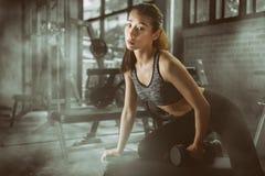 Атлетическая молодая азиатская женщина разрабатывает на спортзале фитнеса стоковое изображение
