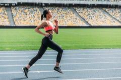 Атлетическая молодая женщина в sportswear sprinting на идущем стадионе следа Стоковая Фотография RF