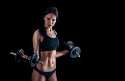 Атлетическая молодая женщина делая разминку фитнеса против черной предпосылки Привлекательная девушка фитнеса нагнетая вверх musc Стоковая Фотография RF