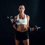 Атлетическая молодая женщина делая разминку фитнеса против черной предпосылки Привлекательная девушка фитнеса нагнетая вверх musc Стоковое фото RF