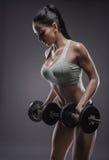 Атлетическая молодая женщина делая разминку фитнеса с гантелями на g стоковые изображения