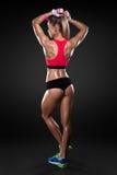Атлетическая молодая женщина показывая мышцы задней части стоковые изображения
