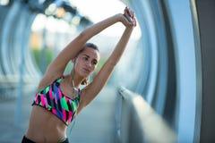 Атлетическая молодая женщина протягивая перед тренировкой пока слушающ к музыке стоковые фото