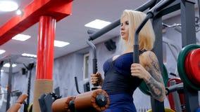 Атлетическая молодая женщина разрабатывая на оборудовании тренировки фитнеса стоковые изображения rf