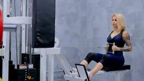 Атлетическая молодая женщина разрабатывая на оборудовании тренировки фитнеса Стоковые Фотографии RF