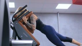 Атлетическая молодая женщина разрабатывая на оборудовании тренировки фитнеса акции видеоматериалы