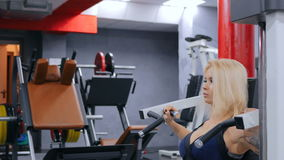 Атлетическая молодая женщина разрабатывая на оборудовании тренировки фитнеса сток-видео