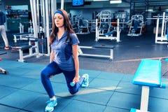 Атлетическая разминка женщины вне сидит на корточках тренировка и гантели держать Стоковое Изображение RF