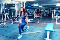 Атлетическая разминка молодой женщины вне сидит на корточках тренировка и dum держать Стоковые Фото