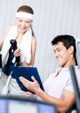 Атлетическая тренировка женщины на имитаторах в спортзале с тренером Стоковая Фотография RF