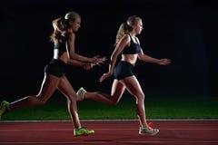 Атлетические бегуны проходя жезл в эстафетном беге Стоковое Изображение
