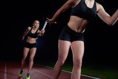 Атлетические бегуны проходя жезл в эстафетном беге Стоковые Изображения