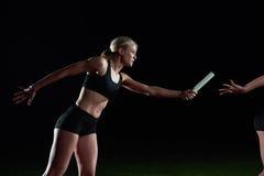 Атлетические бегуны проходя жезл в эстафетном беге Стоковое Фото