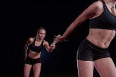 Атлетические бегуны проходя жезл в эстафетном беге Стоковые Изображения RF