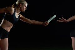 Атлетические бегуны проходя жезл в эстафетном беге Стоковые Фотографии RF