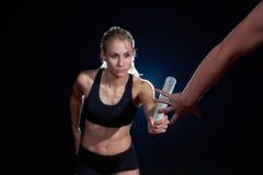 Атлетические бегуны проходя жезл в эстафетном беге Стоковая Фотография