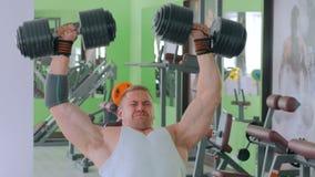Атлетические гантели молодого человека поднимаясь на спортзале сток-видео