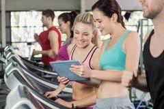 Атлетические женщины смотря таблетку Стоковые Фотографии RF