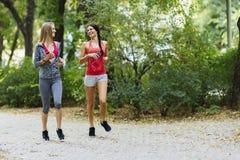 Атлетические женщины jogging в природе Стоковое Изображение RF