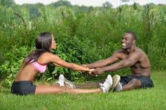 Атлетические и подходящие Афро-американские пары - протягивающ Стоковая Фотография