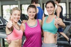 Атлетические усмехаясь женщины представляя с большими пальцами руки вверх Стоковое Изображение RF
