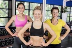 Атлетические усмехаясь женщины представляя с руками на бедрах Стоковые Фотографии RF