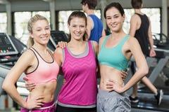 Атлетические усмехаясь женщины представляя с руками на бедрах Стоковая Фотография