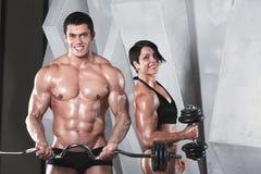 Атлетические человек и женщина с Dumbells Стоковая Фотография