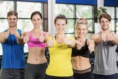 Атлетические люди и женщины представляя с большими пальцами руки вверх Стоковое Изображение RF