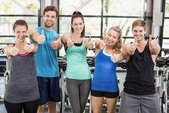 Атлетические люди и женщины представляя с большими пальцами руки вверх Стоковые Фото