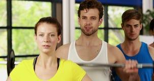 Атлетические люди и женщины разрабатывая видеоматериал