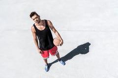 Атлетический баскетболист при шарик стоя на суде Стоковые Изображения
