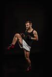 Атлетический бородатый боксер с перчатками на темной предпосылке стоковое изображение rf