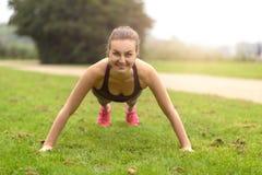 Атлетический делать женщины нажимает вверх тренировку на парке Стоковое фото RF