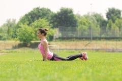 Атлетический живот травы простирания кобры девушки смотря на пол Стоковое Фото