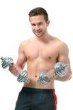 Атлетический молодой человек делая тренировки с гантелями Стоковое фото RF