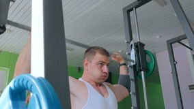 Атлетический молодой человек делая тренировки с штангой на спортзале, фитнес-клубе видеоматериал