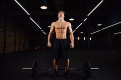Атлетический нагнетенный культурист человека стоит перед баром в спортзале Фитнес мужской подготавливает для работы стоковые фотографии rf