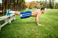 Атлетический построенный человек делая pushups и тренировку ядра в парке Тренировка баскетболиста фитнеса на траве Стоковое фото RF