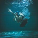 Атлетический пловец делая underwater прыжка кувырком стоковые изображения