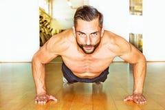 Атлетический человек делать нажимает поднимает Стоковые Фото